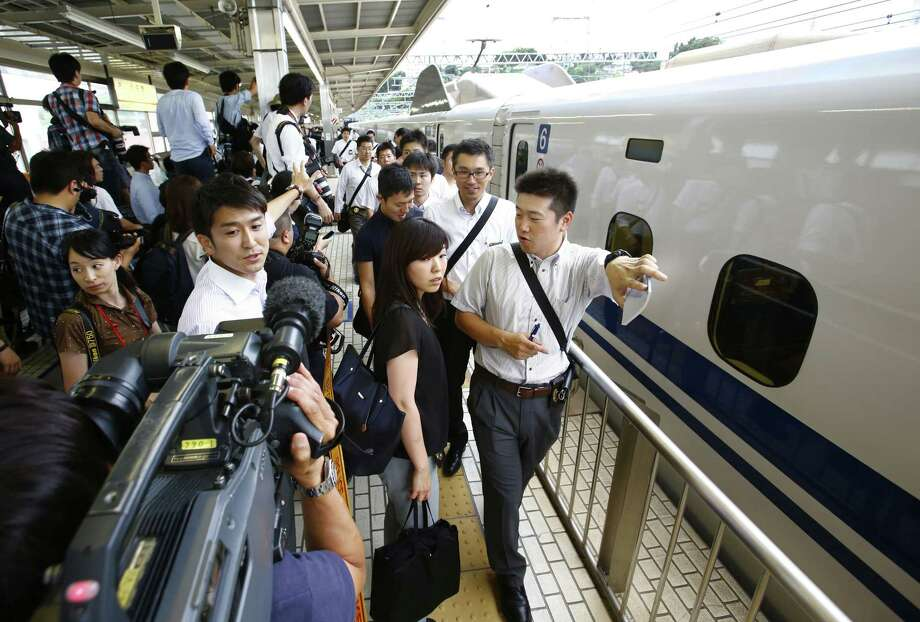 Passengers walk on a platform after getting off a high-speed bullet train where a man set himself of fire, at Odawara station in Odawara, west of Tokyo, Tuesday, June 30, 2015. The man riding the high-speed bullet train set himself on fire Tuesday, killing himself as the coach filled with smoke, Japanese officials and media reports said. (AP Photo/Shizuo Kambayashi) Photo: AP / AP