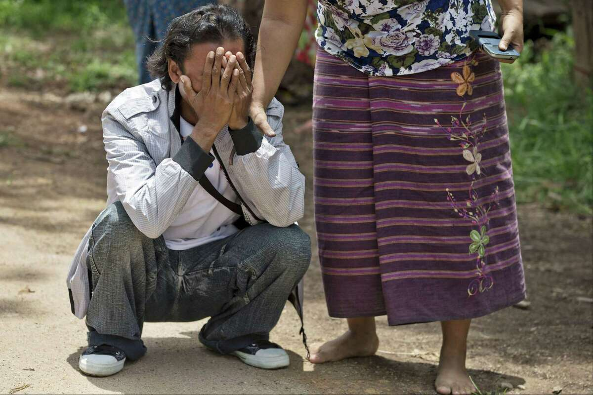 ADVANCE FOR RELEASE WEDNESDAY, JULY 1, 2015, AND THEREAFTER - In this May 16, 2015 photo, former slave fisherman Myint Naing, left, cries as he sees his mother running toward him as they are reunited after 22 years in their village in Mon State, Myanmar. Myint, 40, is among hundreds of former slave fishermen who returned to Myanmar following an Associated Press investigation into the use of forced labor in Southeast Asiaís seafood industry. (AP Photo/Gemunu Amarasinghe)
