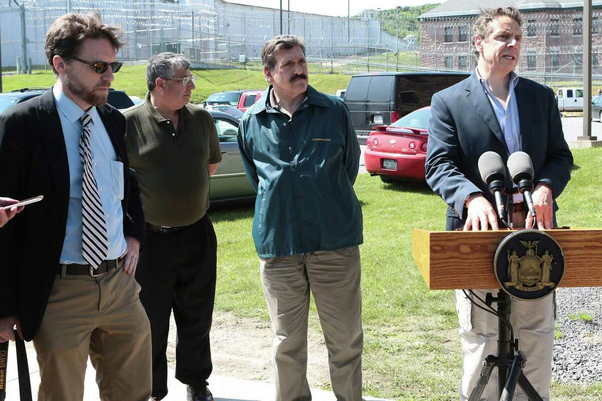 In a Saturday, June 6, 2015 photo, Clinton Correctional Superintendent Steven Racette, second from left, listens to Gov. Andrew Cuomo speak during a press conference in Dannemora, N.Y. Officials said Tuesday that Racette and his deputy in charge of security are among 12 more staff who have been put on administrative leave during the investigation into David Sweat and Richard Matt's escape from the maxiumum-security Clinton Correctional Facility. Acting State Department of Corrections and Community Supervision Commissioner Anthony Annucci is second from right. (Gabe Dickens/The Press-Republican via AP)