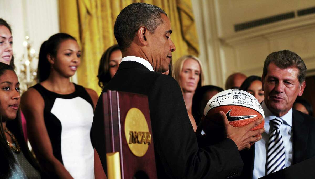 President Barack Obama looks at the basketball that he was given during a ceremony to honor the 2013 NCAA Women�s Basketball Champion team, the University of Connecticut Huskies, Wednesday, July 31, 2013, in the East Room of the White House in Washington, Wednesday, July 31, 2013. UConn head basketball coach Geno Auriemma watches at right. (AP Photo/Susan Walsh)