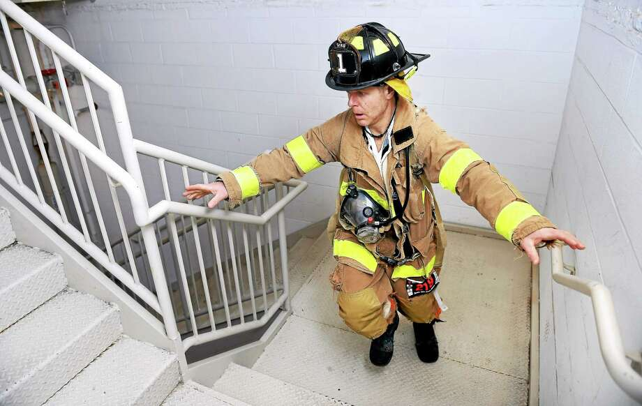 Alan Hagander of the Stamford Fire Department begins the Firefighter Challenge at the Fight for Air Climb Saturday. Photo: Arnold Gold — New Haven Register