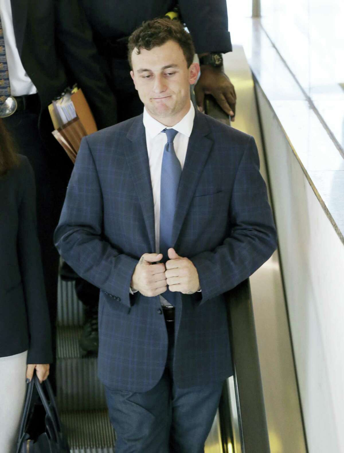 Former Cleveland Browns quarterback Johnny Manziel takes an escalator after making his initial court appearance, Thursday, May 5, 2016, in Dallas. The Heisman Trophy winner and former Texas A&M star was indicted by a grand jury last month after his ex-girlfriend alleged he hit her and threatened to kill her during a night out in January.