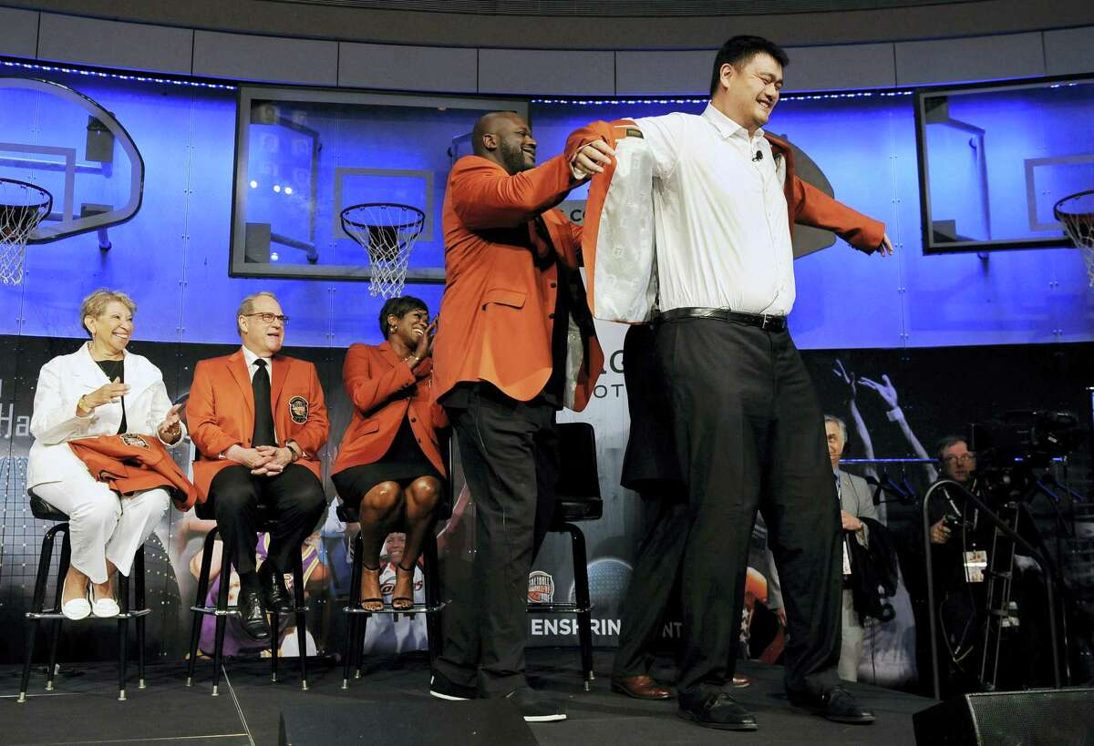 Basketball Hall of Fame inductee Shaquille O'Neal, front left, helps fellow inductee Yao Ming, right, with his jacket during a news conference at the Naismith Memorial Basketball Hall of Fame on Thursday in Springfield, Massachusetts.