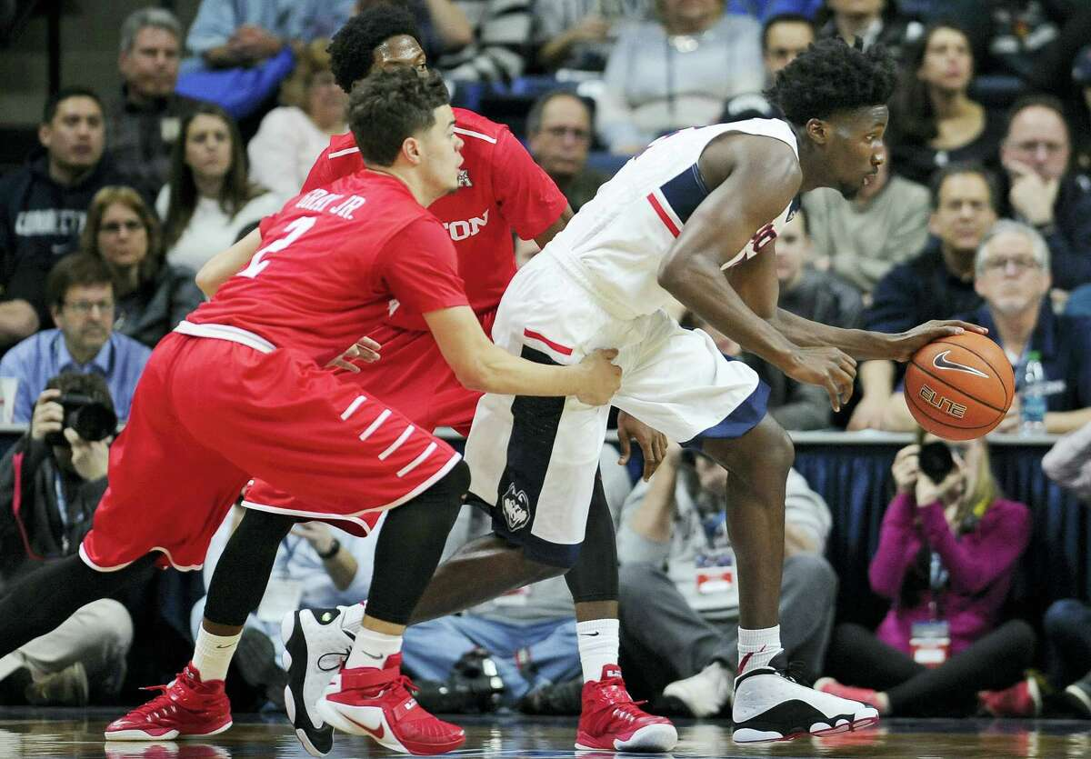 Connecticut's Daniel Hamilton breaks out between Houston's Rob Gray, Jr., left, and Danrad Knowles, back center, in the second half of an NCAA college basketball game, Sunday, Feb. 28, 2016, in Storrs, Conn. Houston won 75-68. (AP Photo/Jessica Hill)