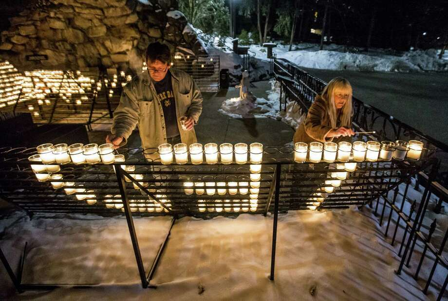 """William Michalski and his wife Rose Michalski, of South Bend, light votives that spell out """"TED"""" as the visit the Grotto of Our Lady of Lourdes on the campus of the University of Notre Dame following the death of former Notre Dame president Rev. Theodore M. Hesburgh, age 97, on Friday, Feb. 27, 2015, in South Bend, Ind. Rose Michalski has worked at Notre Dame for 31 years. (AP Photo/South Bend Tribune, Robert Franklin) Photo: AP / South Bend Tribune"""