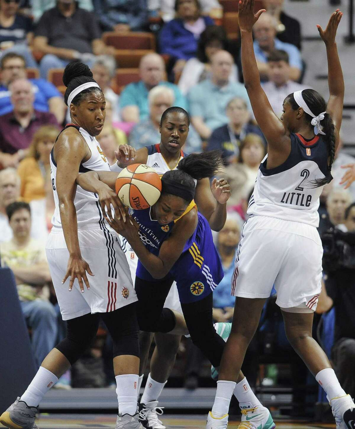 The Los Angeles Sparks' Nneka Ogwumike, center, stumbles under pressure from the Connecticut Sun's Kelsey Bone, left, and Camille Little, right, during a recent game.