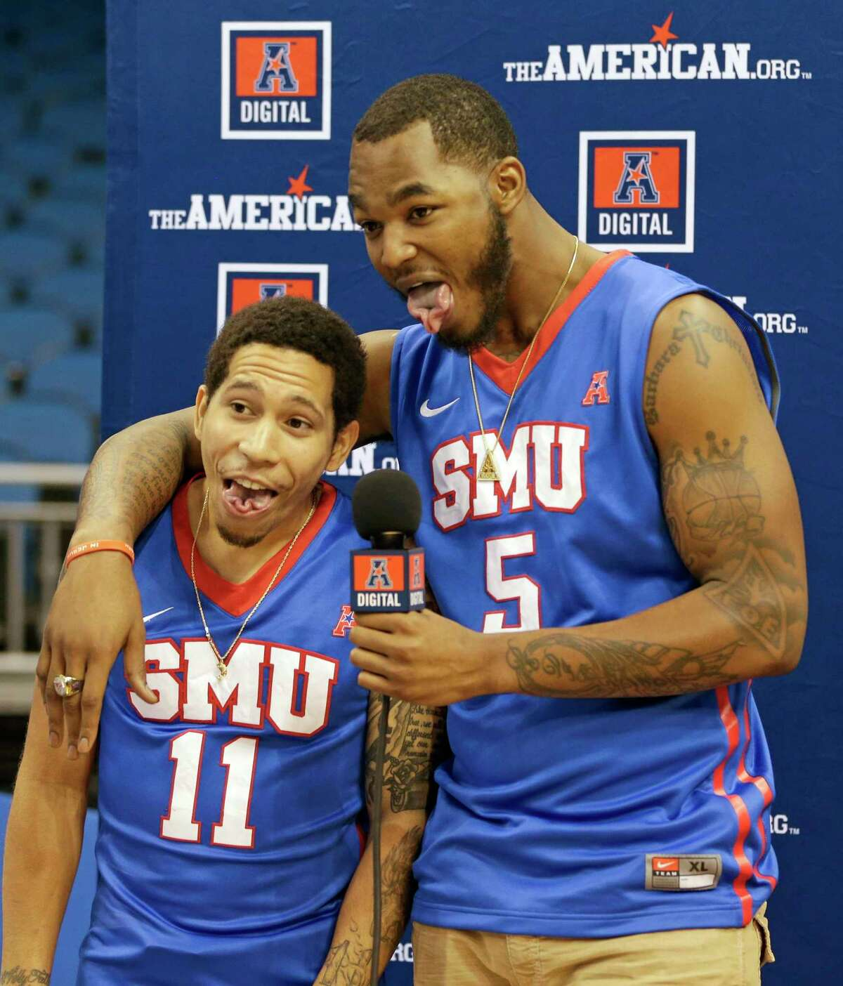 SMU players Nic Moore (11), the preseason player of the year, and Markus Kennedy (5) joke around during AAC media day on Tuesday in Orlando, Fla.