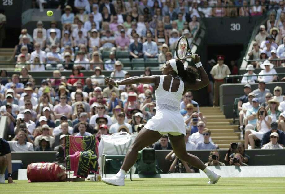 Serena Williams returns a ball to Margarita Gasparyan during their first-round match at Wimbledon on Monday. Photo: Pavel Golovkin — The Associated Press  / AP