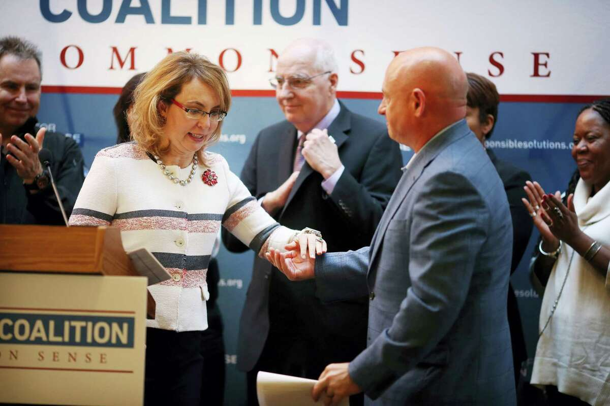 Gabrielle Giffords is helped off the stage by her husband Mark Kelly after speaking during a news conference at Augsburg College in Minneapolis about gun control.