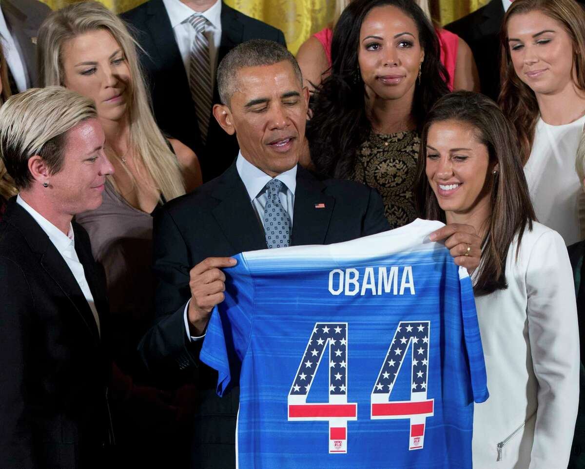 President Barack Obama receives a soccer jersey as he welcomes the U.S. Women's National Soccer Team in the East Room of the White House in Washington on Tuesday. From left are Abby Wambach, Julie Johnston, Obama, Sydney Leroux and Carli Lloyd.