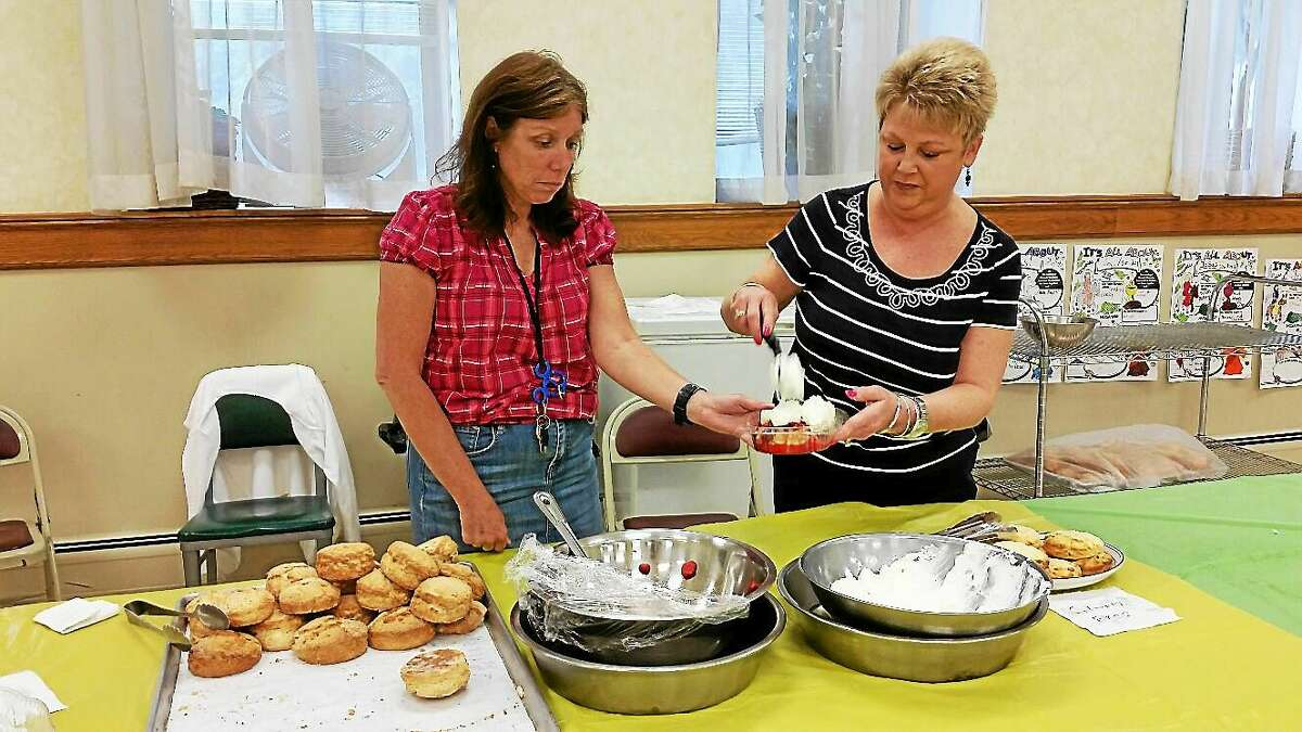 NF Ambery Volunteers Maureen Shepard of Torrington and Beth Lipeika of Litchfield served customers homemade strawberry shortcakes topped with fresh whipped cream at the Center Congregational Church's annual Strawberry Festival Sunday.