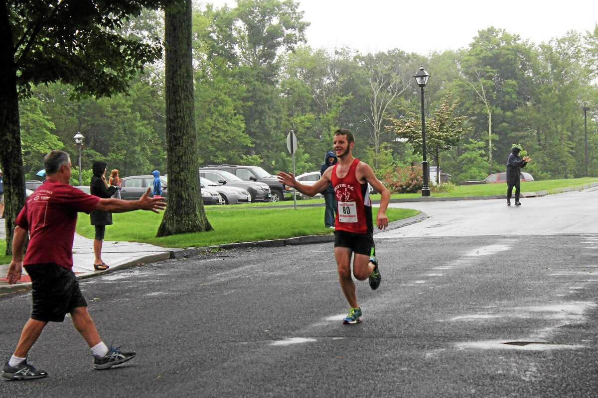 John Neston -- Register-Citizen Max Girouard of Bristol is congratulated at the fiinished line for winning the 5K race.