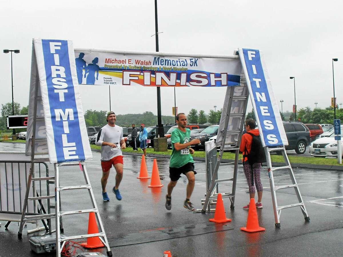 Stephen Underwood -- Register-Citizen Two runners cross the finish line in the rain in East Hartford.