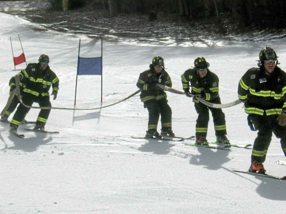 John Torsiello photo The Danbury Fire Department team crosses the finish line. Photo: Journal Register Co.