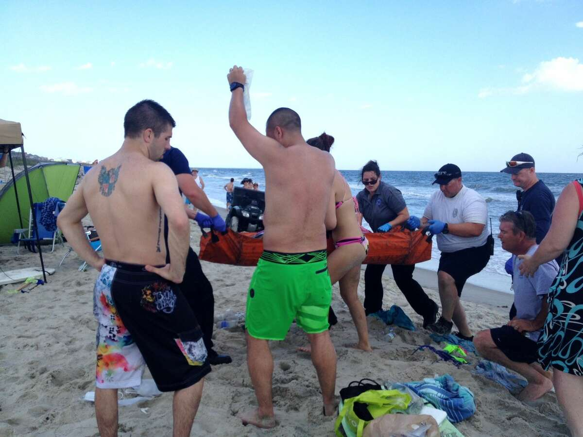 In this June 14, 2015 photo, emergency responders assist a teenage girl at the scene of a shark attack in Oak Island, N.C. Officials say a 17-year-old boy is the latest victim of a shark attack off North Carolina's coast on June 27, 2015, the second attack in as many days and the sixth attack in the past two weeks.