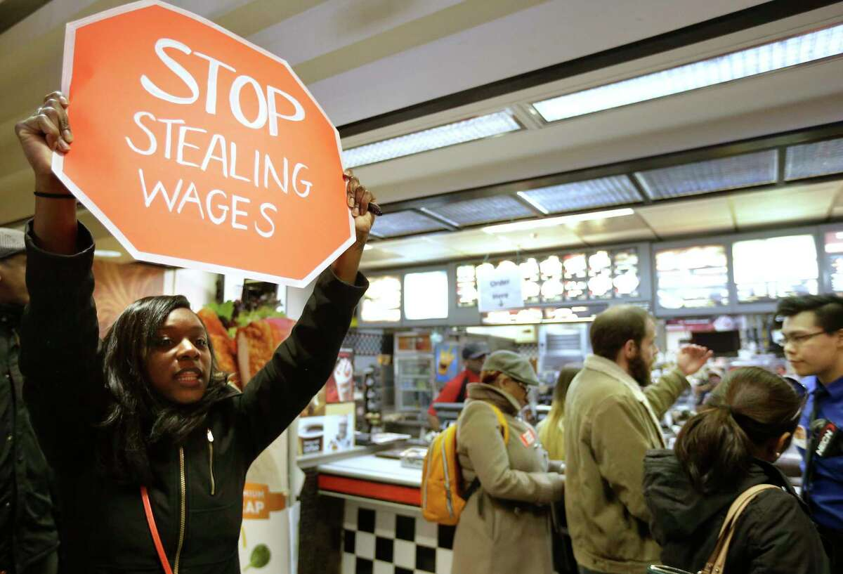Demonstrator Sherae Speight, of Boston, holds a placard and chants during a protest at a McDonalds fast foot restaurant March 18, 2014, in Boston, held to call attention to the denial of overtime pay and other violations protesters say deprive workers of the money they're owed.