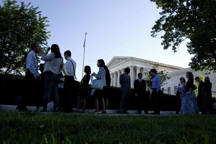 People stand in line hoping to enter the Supreme Court in Washington on Monday, June 29, 2015. The Supreme Court is meeting for the final time until the fall to decide three remaining cases and add some new ones for the term that starts in October. Photo: AP Photo/Jacquelyn Martin  / AP