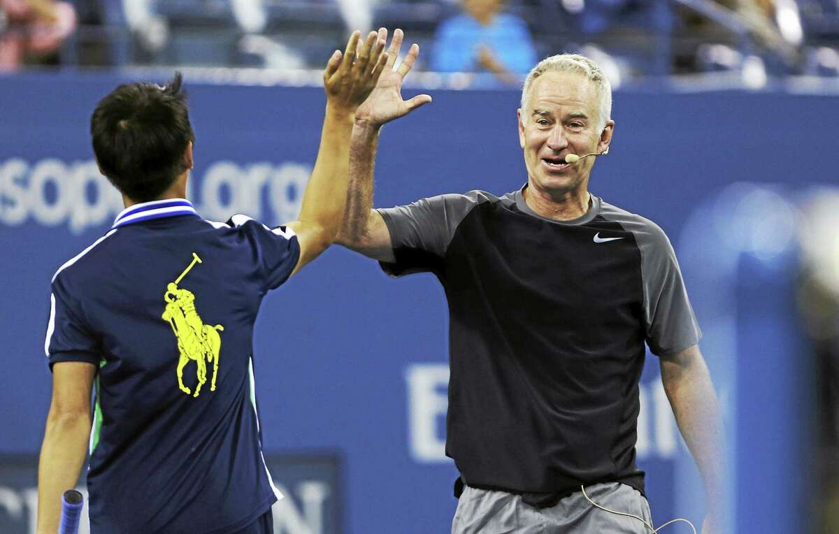 John McEnroe high-fives a ball boy during an exhibition match last September at the U.S. Open in New York.