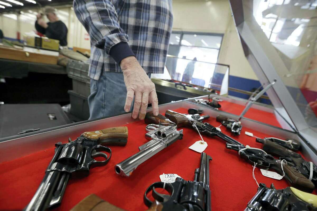 In this Feb. 6, 2015, file photo, a dealer arranges handguns in a display case in advance of a show at the Arkansas State Fairgrounds in Little Rock, Ark.