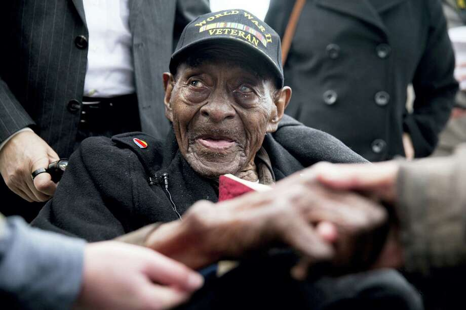 In this Dec. 7, 2015 file photo, Frank Levingston Jr., of Lake Charles, La.,  is greeted by visitors following a wreath laying ceremony to mark the anniversary of Pearl Harbor at the World War II Memorial in Washington. Levingston, a 110-year-old veteran who served in World War II, died Tuesday, May 3, 2016. Photo: AP Photo — Andrew Harnik / 2015 THE ASSOCIATED PRESS
