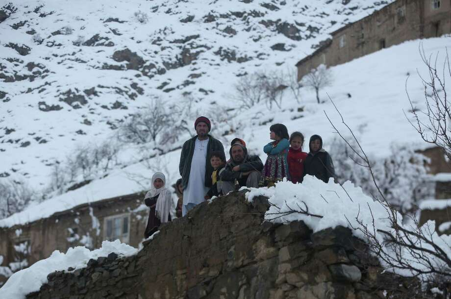 Afghan villagers look on in a village close to an avalanche site in Panjshir province north of Kabul, Afghanistan, Wednesday, Feb. 25, 2015. Avalanches caused by a heavy winter snow killed at least 124 people in northeastern Afghanistan, an emergency official said Wednesday, as rescuers clawed through debris with their hands to save those buried beneath. (AP Photo/Massoud Hossaini) Photo: AP / AP