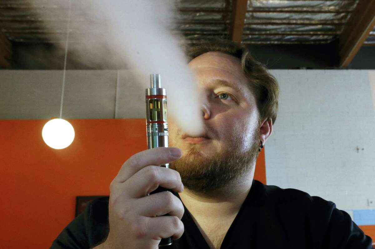 In this July 16, 2015 photo, Bruce Schillin, 32, exhales vapor from an e-cigarette at the Vapor Spot, in Sacramento, Calif.