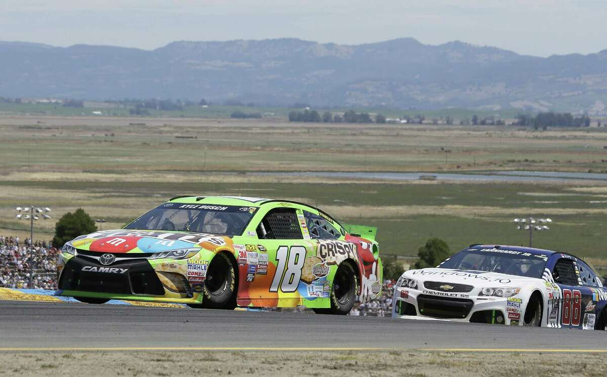 Kyle Busch (18) leads Dale Earnhardt Jr. through turn 2 during the NASCAR Sprint Cup Series race Sunday in Sonoma, Calif. Busch won the race.