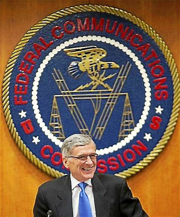 "Federal Communication Commission (FCC Chairman Tom Wheeler  takes his seat before the start of an open hearing in Washington, Thursday, Feb. 26, 2015. Internet service providers like Comcast, Verizon, AT&T, Sprint and T-Mobile would have to act in the ""public interest"" when providing a mobile connection to your home or phone, under new rules being considered by the Federal Communications Commission. The rules would put the Internet in the same regulatory camp as the telephone, banning providers from ""unjust or unreasonable"" business practices.  (AP Photo/Pablo Martinez Monsivais) Photo: AP / AP"