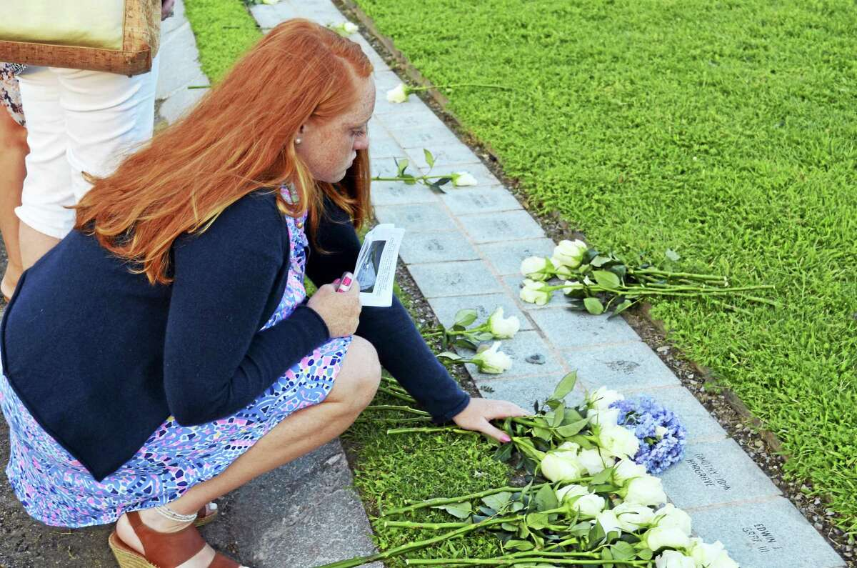 TOM HENRY — WESTPORT MINUTEMAN Emma Hunt, 16, places flowers at the granite stone that honors her father, William Christopher Hunt, who was working in the South Tower of the World Trade Center when it collapsed on Sept. 11, 2001.