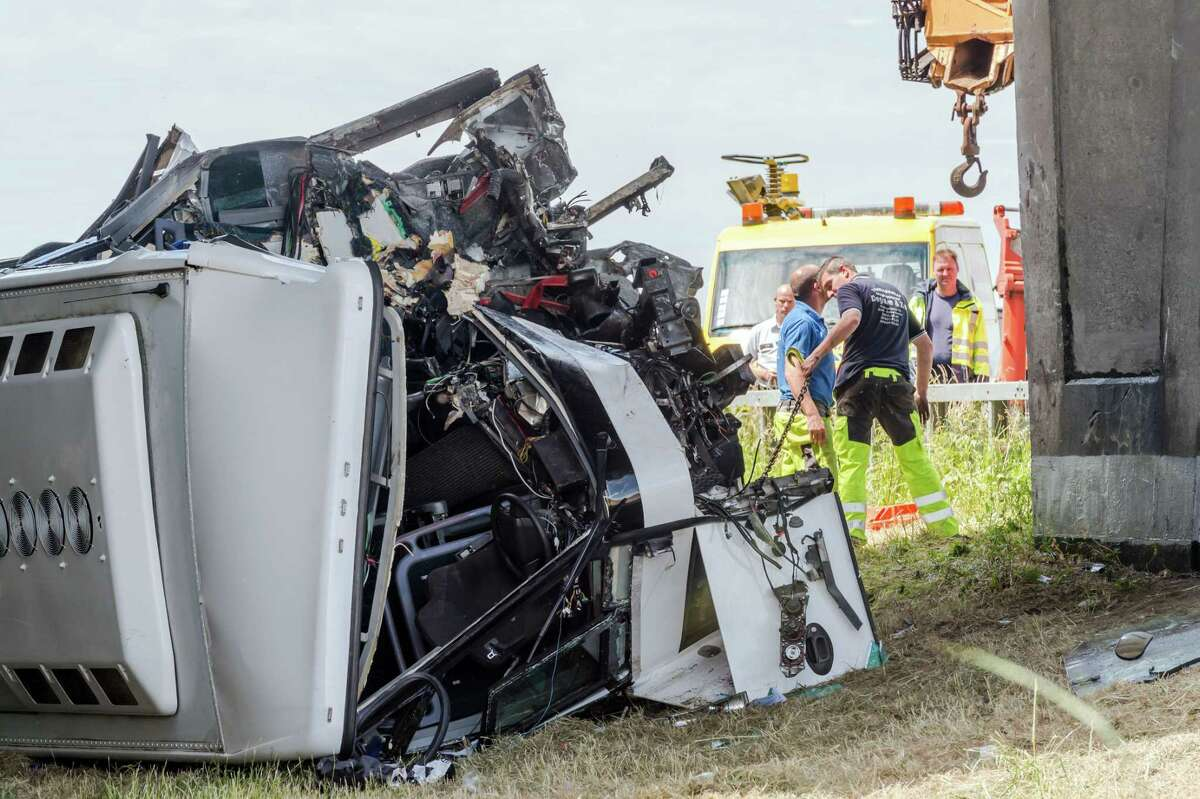 Safety workers attend to a bus which crashed on a motorway in Middlekerke, Belgium on June 28, 2015. The bus, carrying British schoolchildren went off the highway and overturned near the Belgian coast on Sunday, injuring the driver and some of the children and killing one of the adults accompanying them.