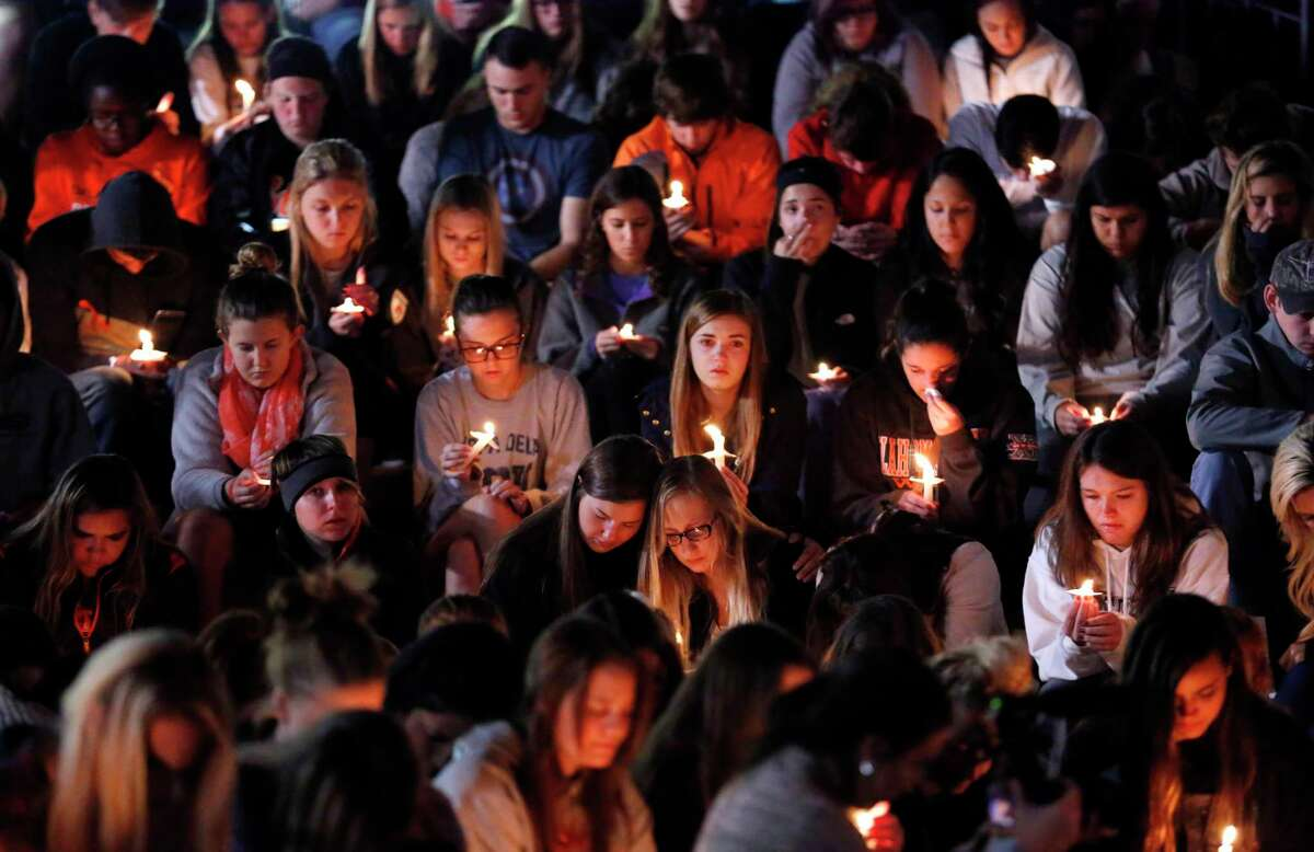People attend a vigil on the campus of Oklahoma State University on Oct. 25, 2015, in Stillwater, Okla. A woman faces second-degree murder charges after authorities said she plowed a car into the crowd at an Oklahoma State homecoming parade on Saturday, killing multiple people, including a toddler.