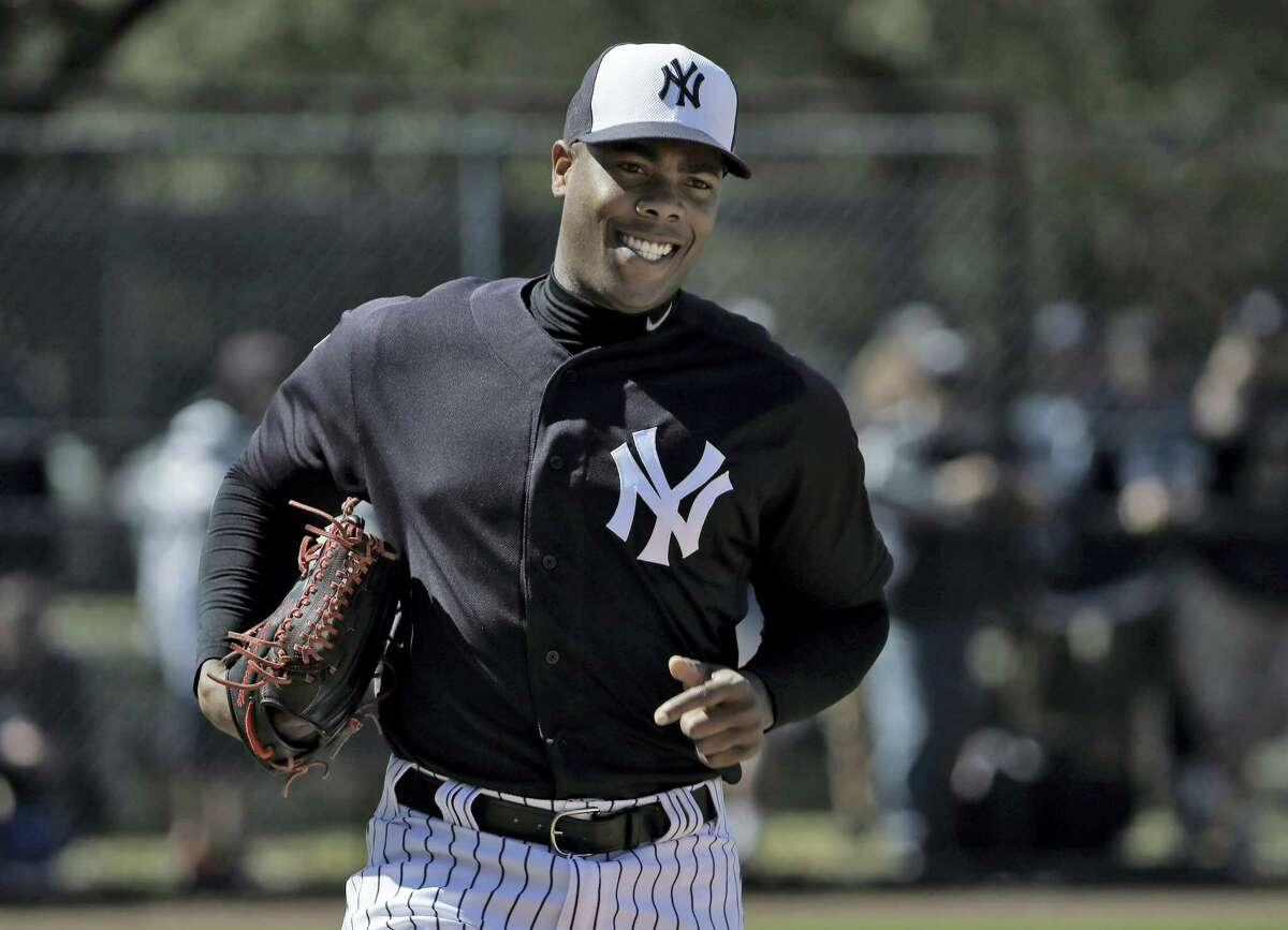 Yankees pitcher Aroldis Chapman smiles as he runs pickoff drills during a workout earlier this spring.
