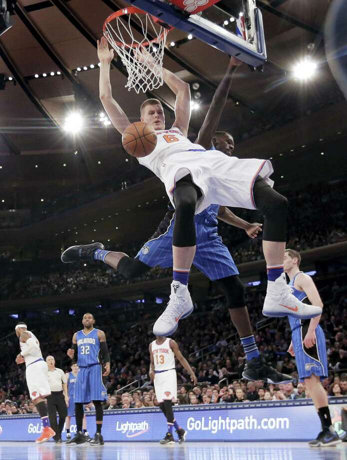 Knicks forward Kristaps Porzingis dunks against Magic center Dewayne Dedmon during the fourth quarter on Friday. Photo: Julie Jacobson — The Associated Press  / AP