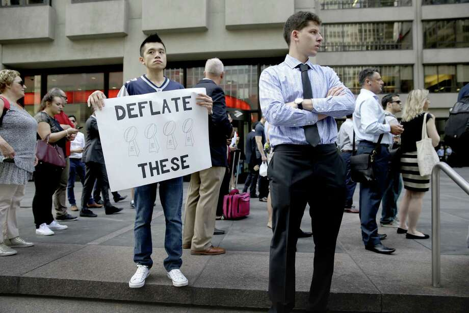 Yan Lin holds a sign supporting New England Patriots quarterback Tom Brady in front of NFL headquarters in New York on Tuesday. It may take NFL Commissioner Roger Goodell a month to render a decision on Brady's appeal. But as Register sports columnist Chip Malafronte points out, we've already wasted five months debating the dumbest scandal in sports history, so what's one more? Photo: Seth Wenig — The Associated Press  / AP