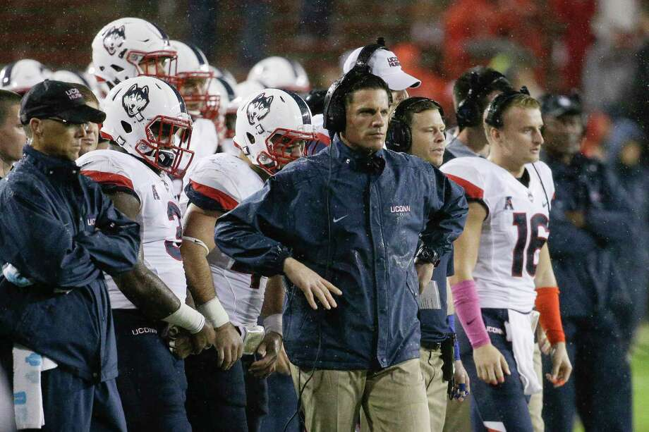 UConn head coach Bob Diaco, center, looks on from the sidelines in the second half against Cincinnati on Saturday, Photo: John Minchillo — The Associated Press  / AP