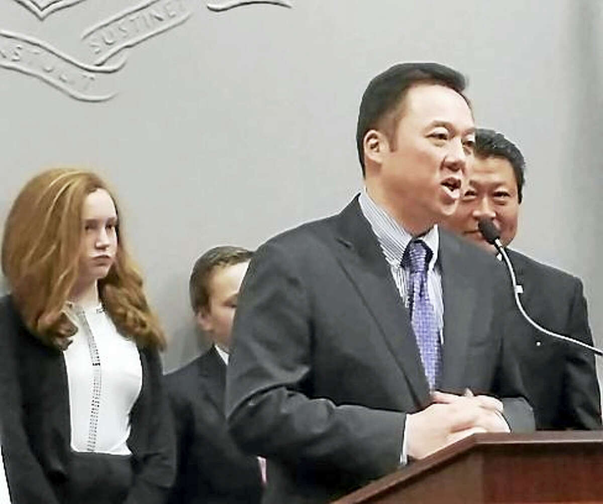 Rep. William Tong speaks to reporters with school children behind him.