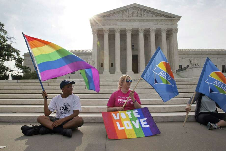 Carlos McKnight, 17, of Washington, left, and Katherine Nicole Struck, 25, of Frederick, Md., hold flags in support of gay marriage outside of the Supreme Court in Washington on Friday. Photo: AP Photo  / AP
