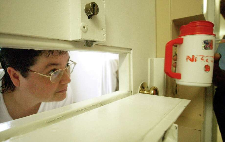 HFM LATE PM FEB 23** FILE -In this Tuesday, July 6, 2004 file photo, Kelly Gissendaner, the only woman on Georgia's death row, peers through the slot in her cell door as a guard brings her a cup of ice at Metro State Prison in Atlanta. Gissendaner, 46, is scheduled to be executed Wednesday, Feb. 25, 2015, at the state prison in Jackson. She was convicted of murder in the 1997 slaying of her husband, Douglas Gissendaner. (AP Photo/Atlanta Journal-Constitution, Bita Honarvar) Photo: AP / AJC