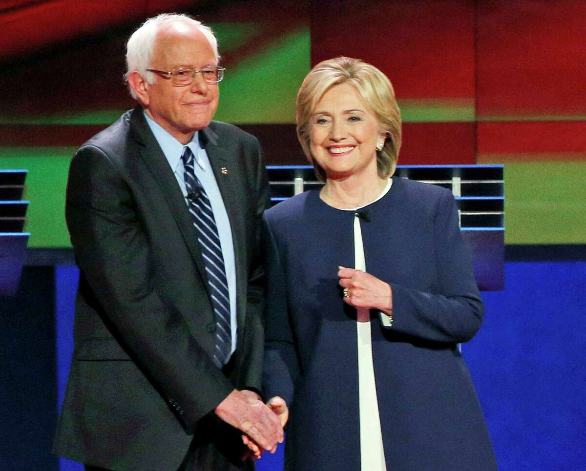 In this Oct. 13, 2015 photo, Democratic presidential candidates Sen. Bernie Sanders, I-Vt., left, and Hillary Rodham Clinton talk before the CNN Democratic presidential debate in Las Vegas. The vast majority of Democrats have a favorable view of Clinton, according to a new Associated Press-GfK poll that shows her recovering lost ground within her own party since the summer. Democrats are divided on whether Sanders could win a general election, with 52 percent saying he could and 46 percent saying he could not.