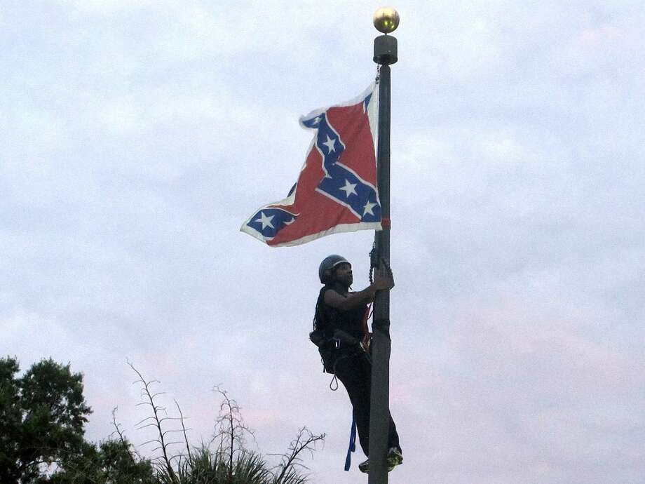 Bree Newsome of Charlotte, N.C., climbs a flagpole to remove the Confederate battle flag at a Confederate monument in front of the Statehouse in Columbia, S.C., on Saturday, June, 27, 2015. She was taken into custody when she came down. The flag was raised again by capitol workers about 45 minutes later.  (AP Photo/Bruce Smith) Photo: AP / AP