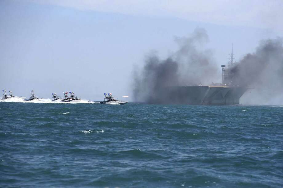 In this picture released by the semi-official Iranian Fars news agency on Wednesday, Feb. 25, 2015, Revolutionary Guard speedboats assault a replica of a U.S. aircraft carrier during large-scale naval drills near the entrance of the Persian Gulf, Iran. Photo:  (AP Photo/Fars News Agency, Hamed Jafarnejad) / Fars News Agency