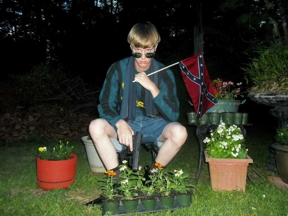 This undated file image that appeared on Lastrhodesian.com, a website being investigated by the FBI in connection with Charleston, S.C., shooting suspect Dylann Roof, shows Roof posing for a photo while holding a Confederate flag. Photo: Lastrhodesian.com Via AP, File  / Lastrhodesian.com