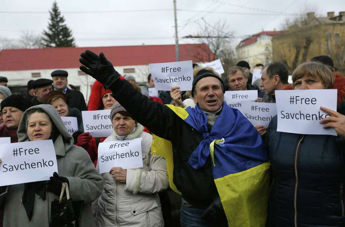 People shout slogans in support of Ukrainian pilot Nadezhda Savchenko during a rally outside the Russian Embassy in Kiev, Ukraine, Tuesday, Feb. 24, 2015. Ukrainian pilot Nadezhda Savchenko was captured by Russia-backed rebels during fighting in eastern Ukraine. The Kiev government has so far been unsuccessful in seeking the extradition of Savchenko who was elected a member of the Ukrainian parliament in the October 2014 Ukrainian parliamentary election. (AP Photo/Sergei Chuzavkov)