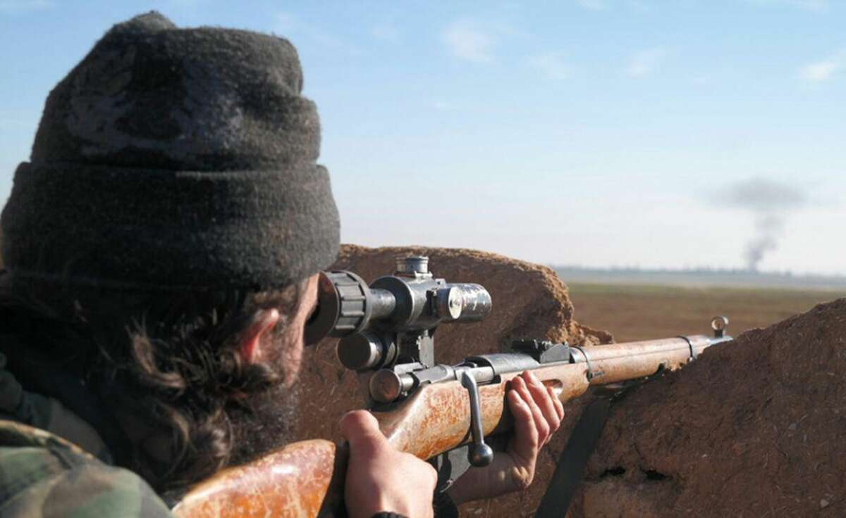 In this image posted on a militant social media account by the Al-Baraka division of the Islamic State group on Tuesday, Feb. 24, 2015, a militant fighter aims a sniper rifle during during fighting in Tal Tamr, Hassakeh province, Syria. Fierce fighting between Kurdish and Christian militiamen and Islamic State militants is continuing on Wednesday, Feb. 25 in northeastern Syria where the extremist group recently abducted at least 70 Christians. (AP Photo via militant social media account)