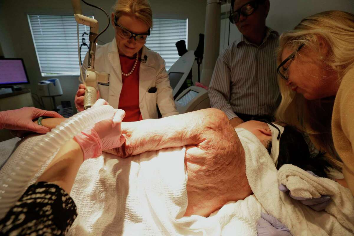 In this Sept. 26, 2015 photo, Dr. Jill Waibel, left, applies a laser to the arm of Kim Phuc to reduce the pain and appearance of her burn scars in Miami. Phuc's husband, Toan Huy Bui, stands at center with patient care coordinator, Deborah Lomax, right.