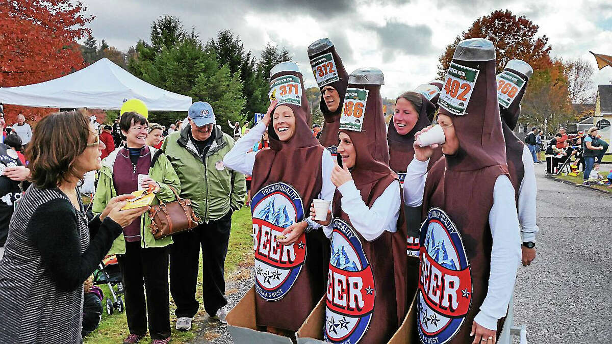 """""""The Six Packs,"""" a group of costumed runners organized by Kevin and Kim Tessier, won the Best Costume Award at the five-mile 39th Annual Kent Pumpkin Run."""