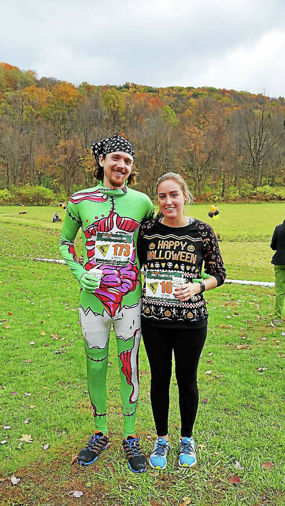 Simon Hawkins of New Canaan and Whitney Lewis of Darien pause after the Pumpkin Run Sunday.