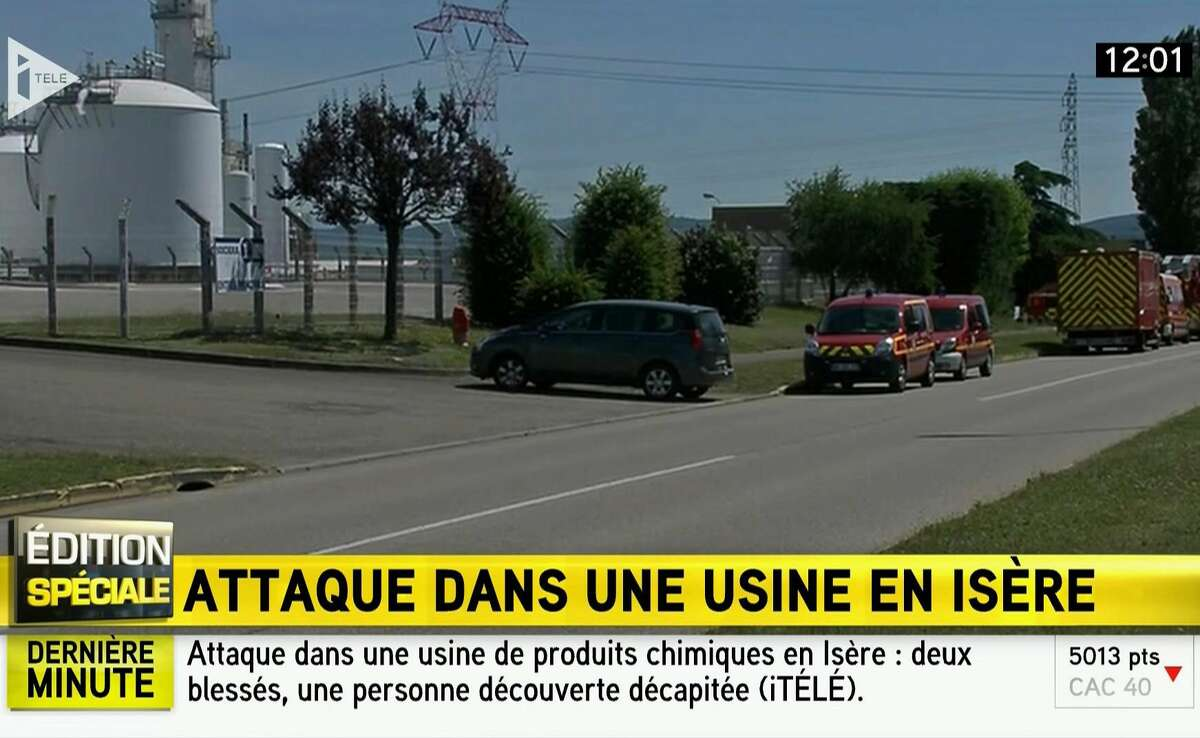 In this screen grab taken from video provided by I Tele, emergency services at the scene outside a factory where a man was allegedly beheaded, in Saint-Quentin-Fallavier, France, Friday, June 26, 2015. French authorities have opened an investigation after an attack and explosion at a gas factory that left one person decapitated and several wounded. Banners with Arabic inscriptions were found near the body, an official said. (I Tele via AP)