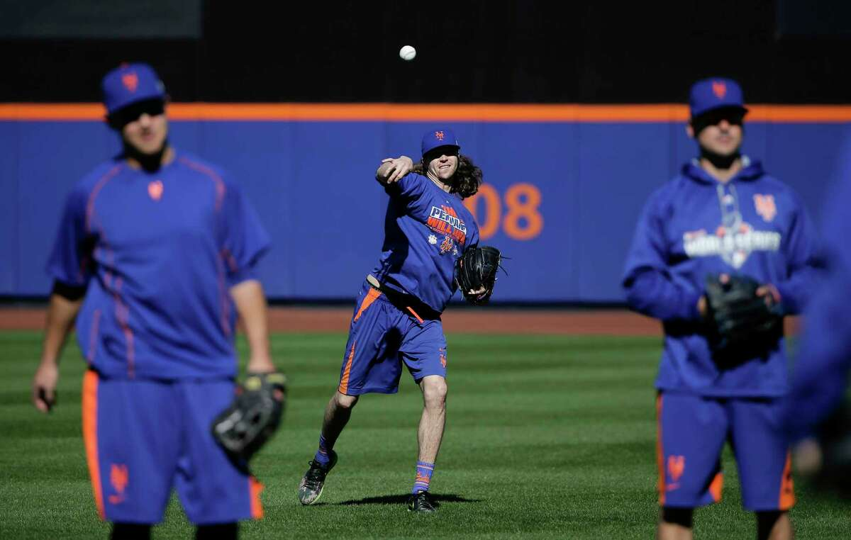 New York Mets starting pitcher Jacob deGrom throws in the outfield during a voluntary workout Friday in New York.