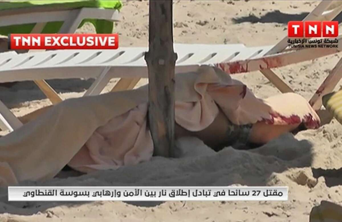 In this screen grab taken from video provided by TNN, a body is covered on a Tunisian beach, in Sousse, Tunisia, Friday June 26, 2015. Two gunmen rushed from the beach into a hotel in the Tunisian resort town of Sousse Friday, killing at least 27 people and wounding six others in the latest attack on the North African country's key tourism industry, the Interior Ministry said. (TNN via AP) MANDATORY CREDIT
